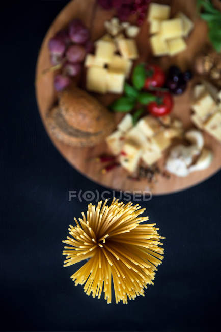 Spaghetti and chopping board with variety of Italian cheeses — Stock Photo