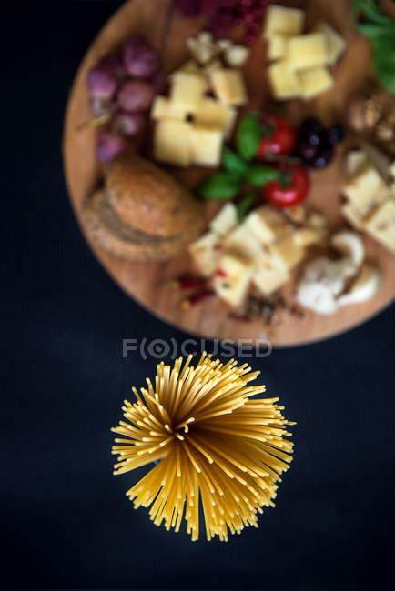 Спагетти и разделочная доска с различных итальянских сыров — стоковое фото
