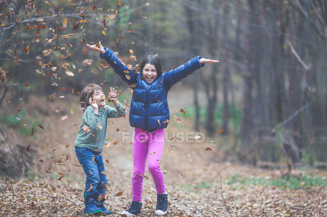 Brother and sister in casual clothing having fun in forest at autumn season — Stock Photo