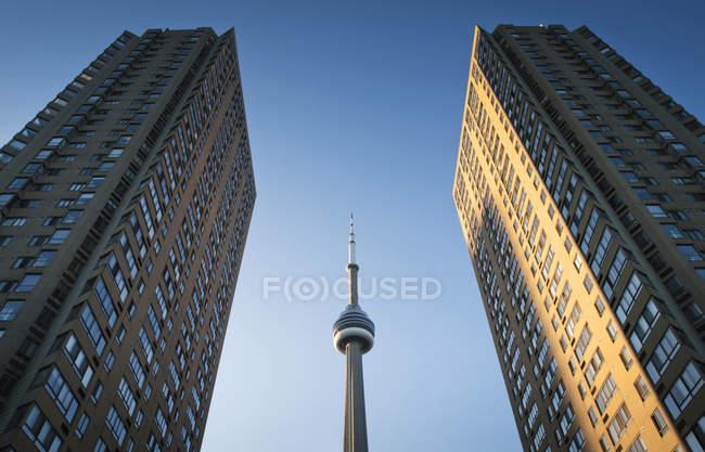 Vista de ángulo bajo de la torre de Cn, enmarcado entre dos rascacielos, Toronto, Ontario, Canadá - foto de stock