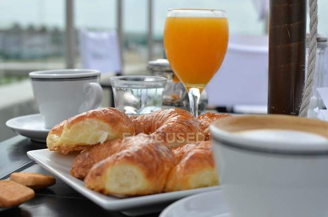 Croissants and orange juice at breakfast at kitchen table — Stock Photo