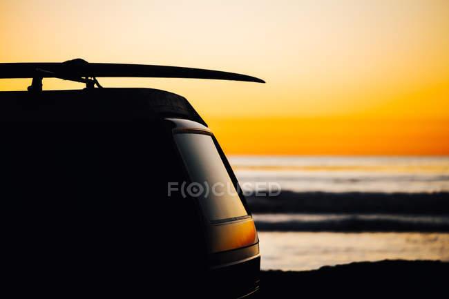 Silueta de coche con tabla de surf en el techo contra la hermosa puesta de sol en San Diego, California, América, Estados Unidos - foto de stock