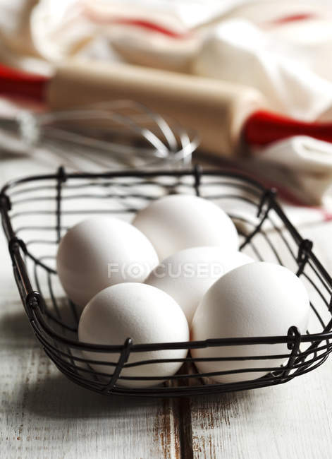Five fresh eggs in a basket on white wood — Stock Photo