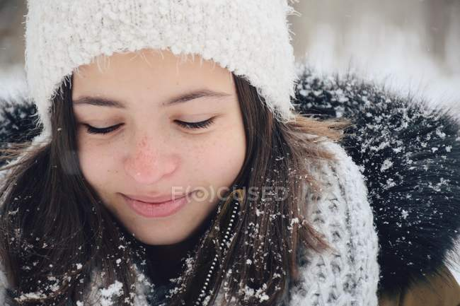 Portrait of a girl wearing warm clothing smiling in snow — Stock Photo