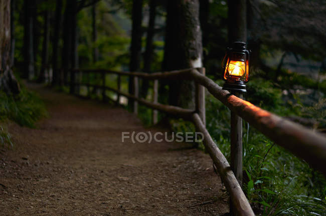 Illuminated oil lamp on fence along woodland path — Stock Photo