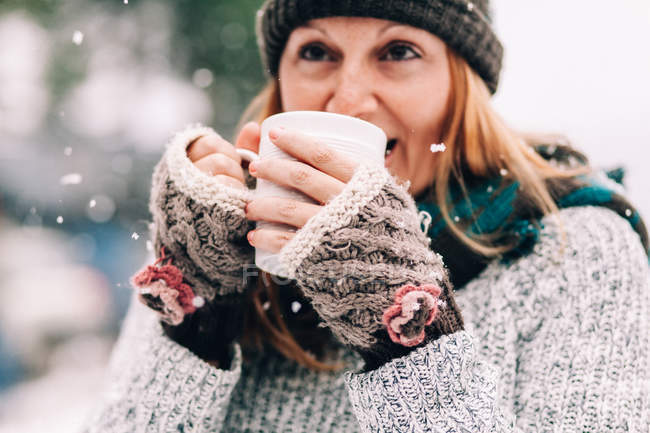 Woman standing in snow and holding hot drink — Stock Photo