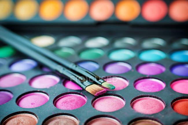 Primer plano de varios colores sombra de ojos paleta y pinceles de maquillaje - foto de stock