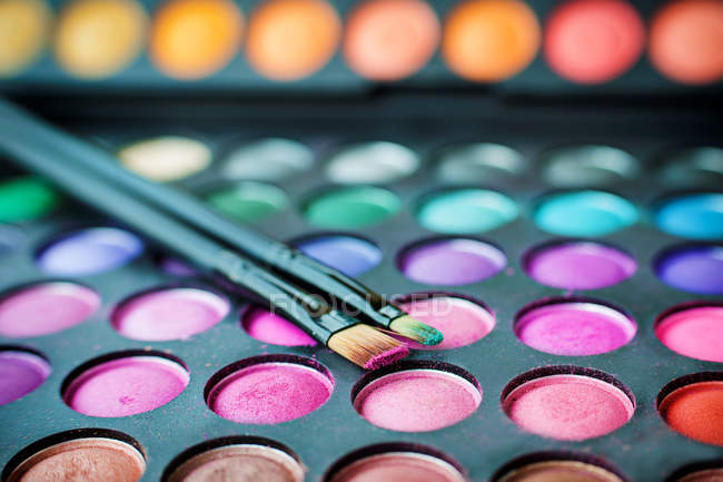 Close-up of multi-colored eyeshadow palette and make up brushes — Stock Photo