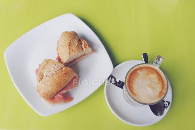Чашка кофе и вкусная ветчина ролл, вид сверху — стоковое фото