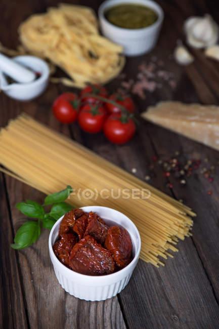 Паста, песто, чеснок, помидоры и пармезан на деревянный стол — стоковое фото