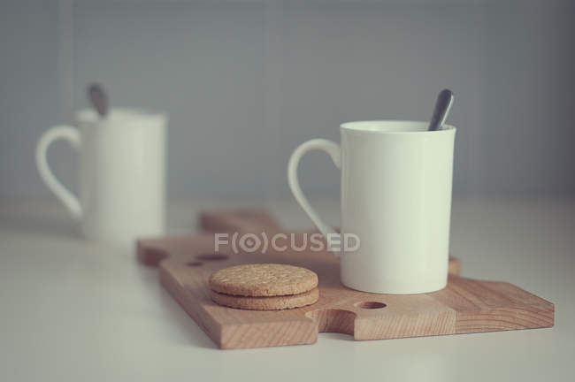 Two coffee cups and biscuits on chopping board. selective focus — Stock Photo