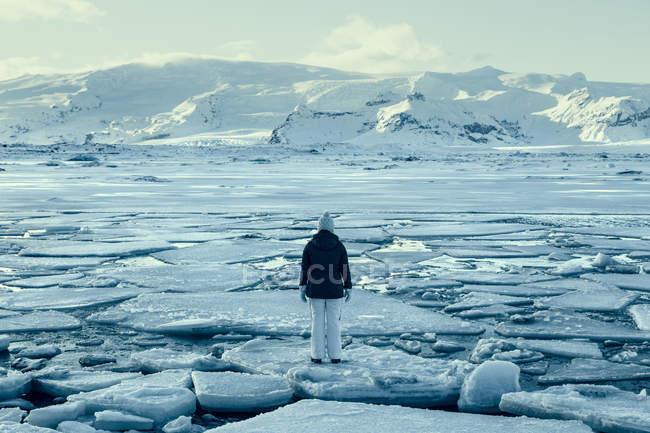 Femme debout sur la banquise sur un lac gelé, Islande — Photo de stock