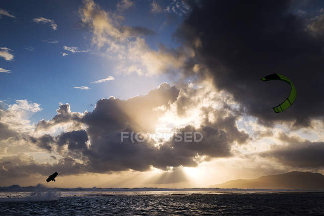 Silhouette of kite-surfer in cloudy sky over sea — Stock Photo