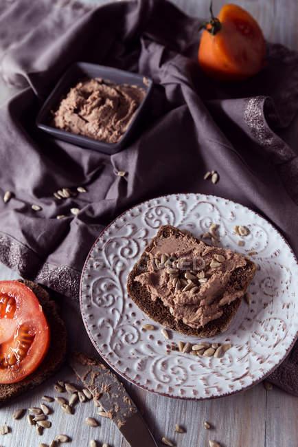 Ржаной хлеб с паштет из печени, помидор и семян подсолнечника — стоковое фото