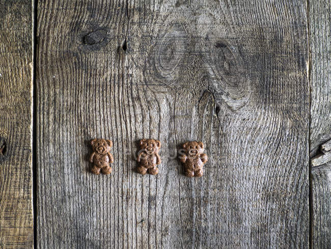 Three chocolate bear cookies on a wooden table — Stock Photo
