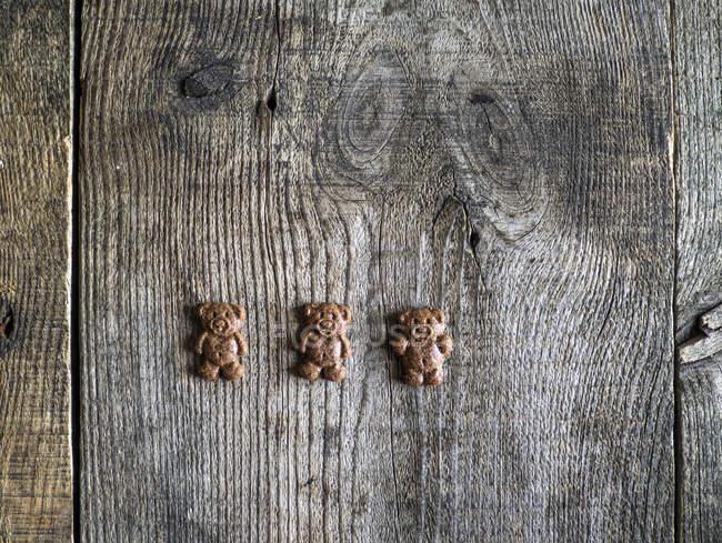 Медведь, три шоколад печенье на деревянном столе — стоковое фото