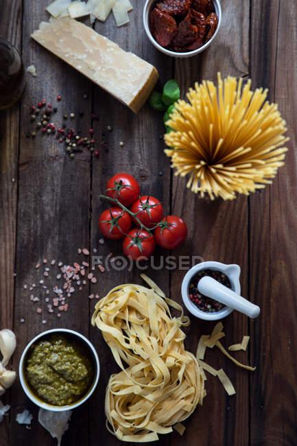 Pasta, Pesto, Knoblauch, Tomaten und Parmesan auf Tisch, Ansicht von oben — Stockfoto