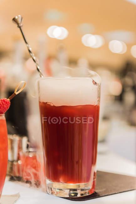 Cocktail de jus de fruits sur table avec fond flou — Photo de stock