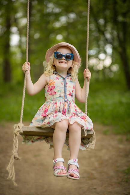 Девушка в солнечных очках сидит на качелях — стоковое фото