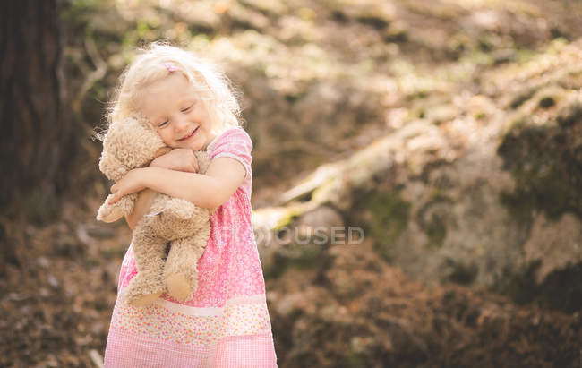 Girl hugging a teddy bear outdoors — Stock Photo