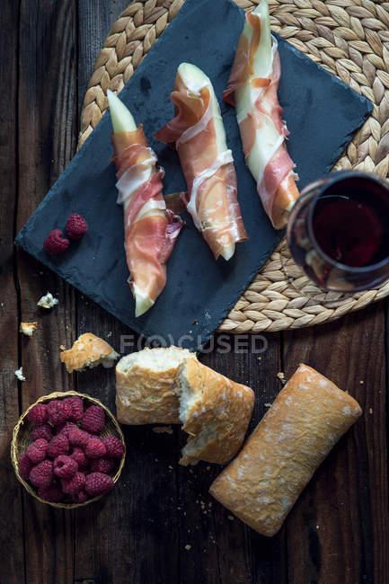 Melão enrolado em presunto de parma com pão, vista superior — Fotografia de Stock