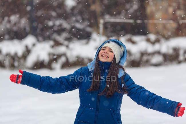 Mädchen mit ausgestreckten Armen spielen im Schnee — Stockfoto