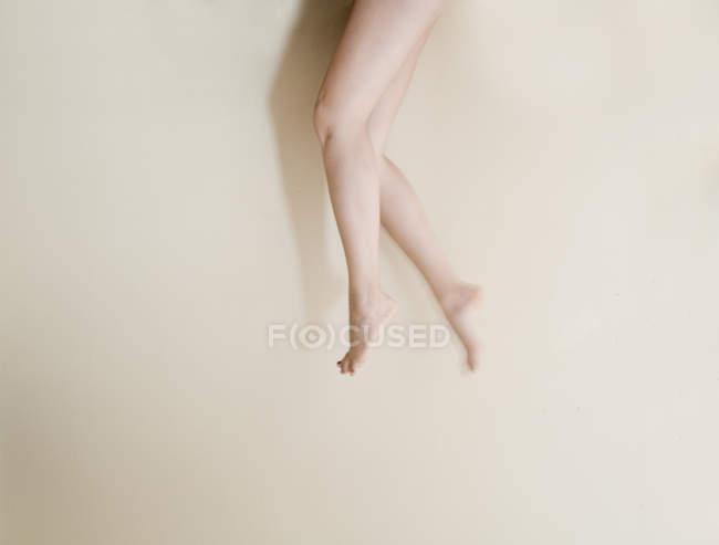 Faible section de jeunes femmes jambes sur fond beige — Photo de stock