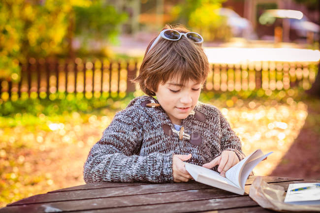 Boy reading book at wooden table in park — Stock Photo