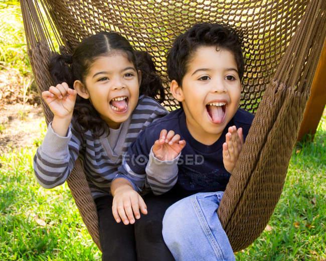 Брат-близнец и сестра сидят в гамаке и строят смешные рожи — стоковое фото
