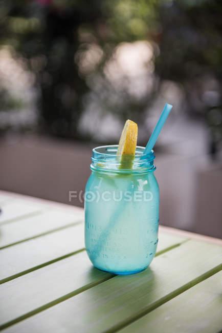 Стакан воды с лимоном на таблицы против размытый фон — стоковое фото