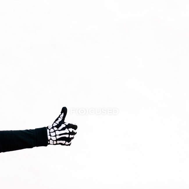 Рука носить скелет наряд делает большие пальцы вверх знак, белый фон — стоковое фото