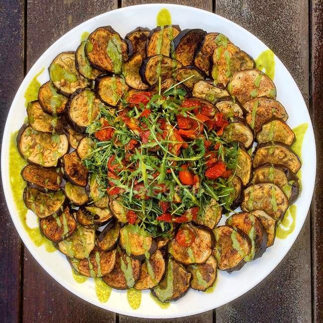 Roasted eggplant salad with tomatoes and basil oil, top view — Stock Photo