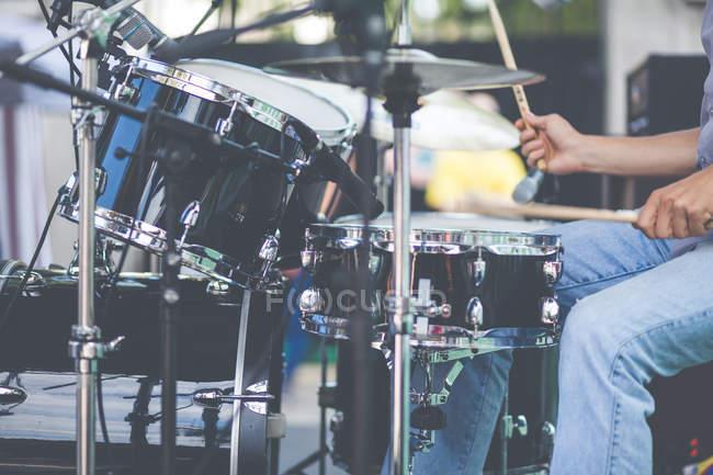 Обрезанное изображение человека играть на барабанах на сцене — стоковое фото