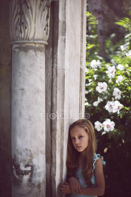 Sad girl leaning column in garden — Stock Photo