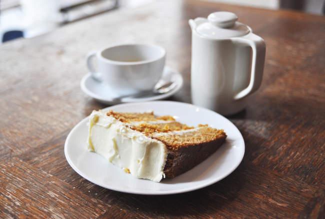 Фарфоровый чайник, Кубок и табличка с морковный торт на деревянный стол в баре — стоковое фото