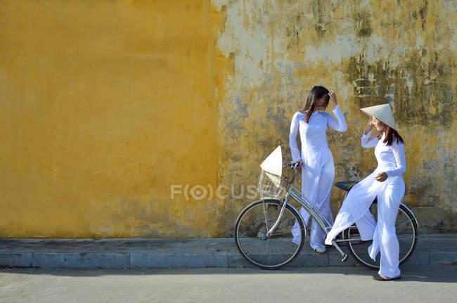 Дві жінки у традиційний одяг стоячи з велосипеда на вулиці і говорити, Хой В'єтнам — стокове фото