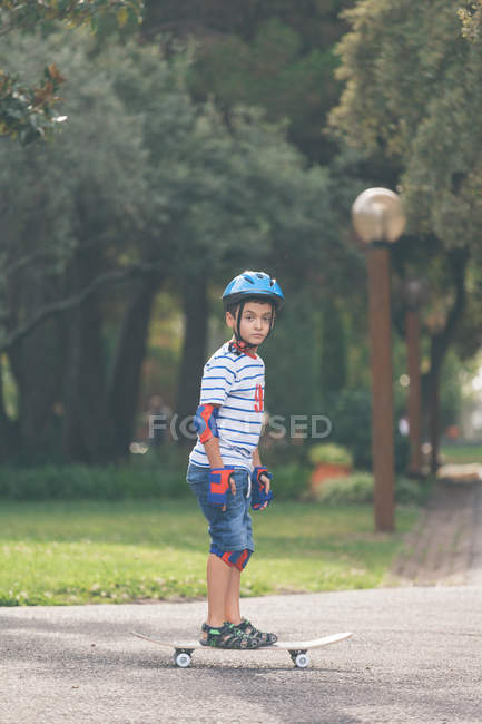 Niño de pie en el monopatín en el parque y mirando a la cámara - foto de stock