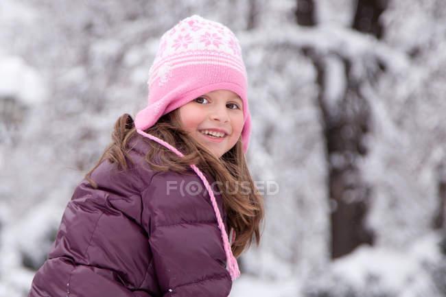 Smiling girl sitting in park in winter — Stock Photo