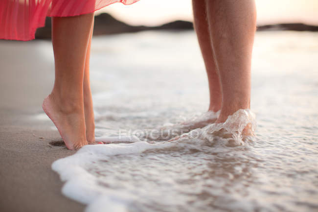 Кадроване зображення пара стоять у воді на пляжі — стокове фото