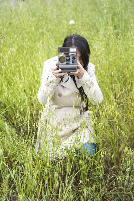 Woman taking photo with vintage instant camera in field — Stock Photo