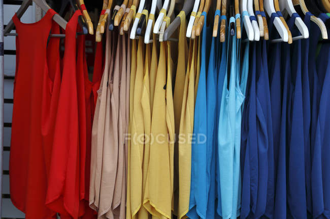Multi-colored vests hanging in market — Stock Photo
