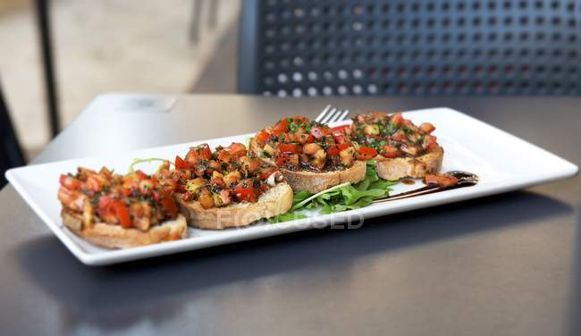 Plaque blanche de bruschetta tomate — Photo de stock