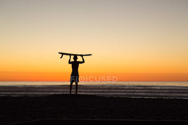 Silhouette of Man standing on beach at sunrise holding longboard above his head — Stock Photo