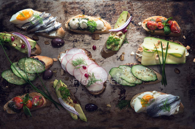 Selection of different tasty bruschetta appetizers over rustic background, top view — Stock Photo