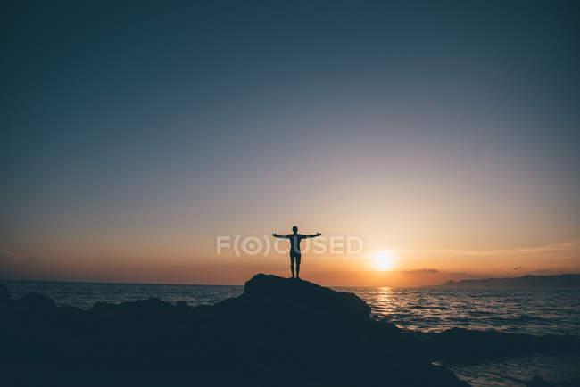 Silhouette eines Mannes stehen auf Felsen mit ausgestreckten Armen — Stockfoto