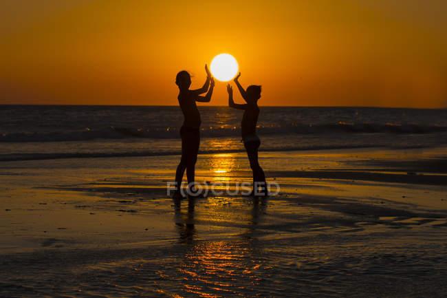 Вид на море молодих друзів тримає сонце на пляжі на заході сонця — стокове фото