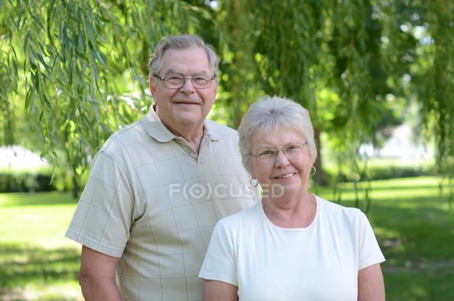 Porträt eines älteren kaukasischen Paares, das im Park lächelt — Stockfoto