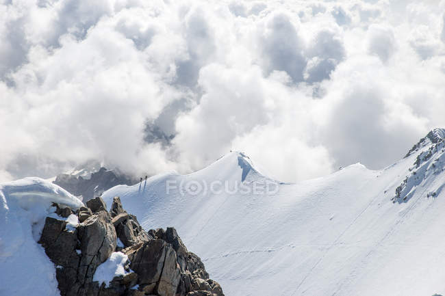 Два человека, прогуливающиеся по горному хребту в швейцарских Альпах, Пиз-Бернина, Швейцария — стоковое фото