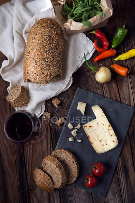 Queijo, pão, vinho tinto e pimenta sobre a mesa de madeira, vista superior — Fotografia de Stock