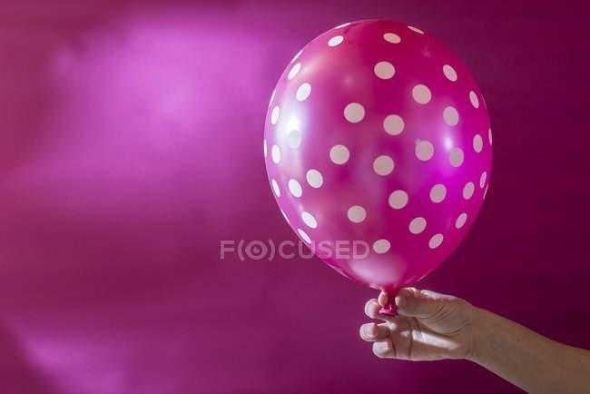 Рука держит розовый шарик с белыми точками польки — стоковое фото